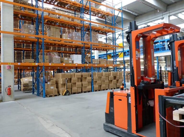 Logistiek heftruck in magazijn met dozen in stellingen